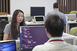 Students talking over the top of a computer monitor