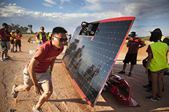 Student running past a solar car being fixed.
