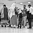 Black and white thumbnail of people standing at an airport.