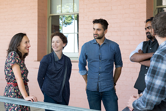 A group of 5 HDR students stand in a semi-circle on the veranda of the ICS building.