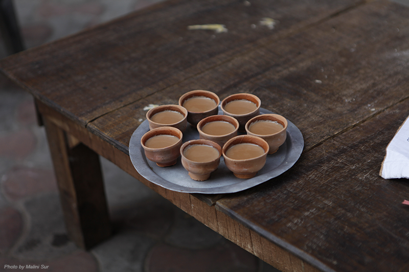8 small clay teacups with tea in them sit on a round metal plate on a wooden table.