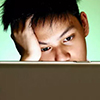 A boy behind a laptop screen