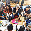 Thumbnail image of a group of young people at a table with books.
